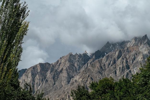 Wolken bedekt sneeuw bedekte bergtoppen in karakoram bereik. gilgit baltistan, pakistan. Premium Foto