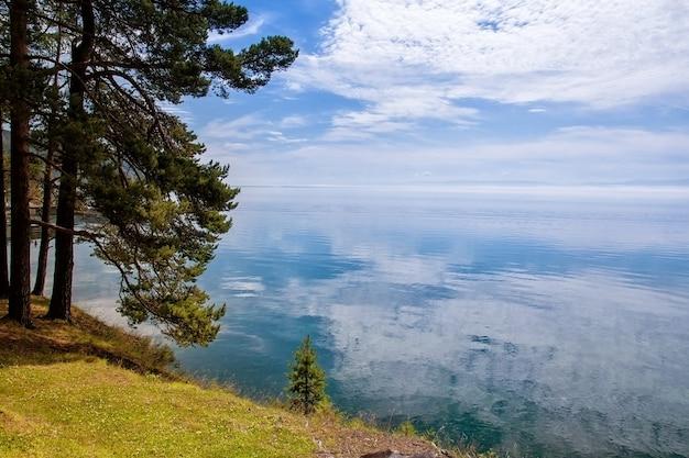 Wolken met reflectie op het water met dennen, baikalmeer Premium Foto