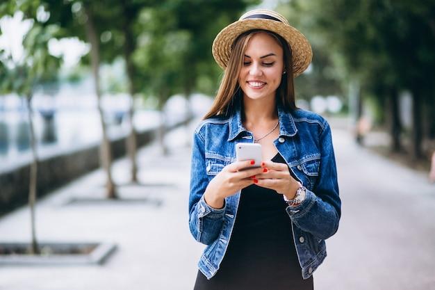 Womanwearing jurk en hoed buiten in park met telefoon Gratis Foto