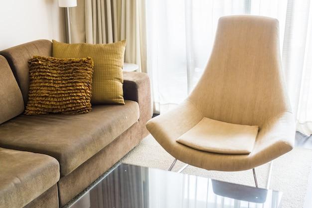 Woonkamer met een bank met kussens en een comfortabele stoel foto