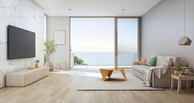 Woonkamer met zeezicht van luxe strandhuis met glazen deur en houten terras. Premium Foto