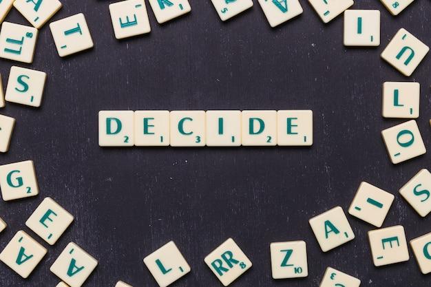 Woord beslissen scrabble letters over zwarte achtergrond Gratis Foto
