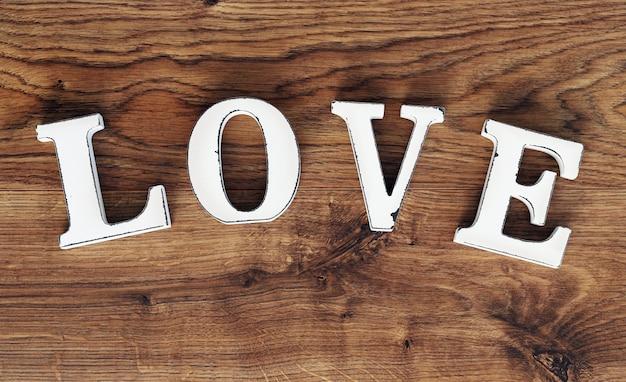 Woord liefde op houten tafel Gratis Foto