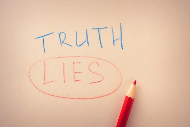 Woord van de waarheid en een onderstreepte leugen, geschreven in kleurpotloden op papier Premium Foto