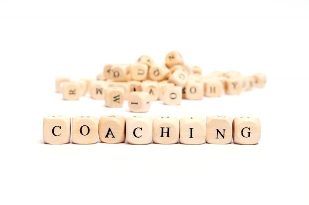 Word met dobbelstenen op witte achtergrond-coaching Premium Foto