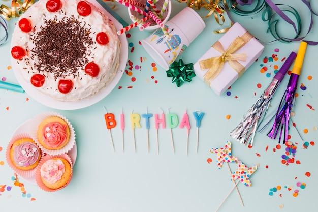 Word verjaardagskaarsen met partijtoebehoren en cake op blauwe achtergrond Gratis Foto
