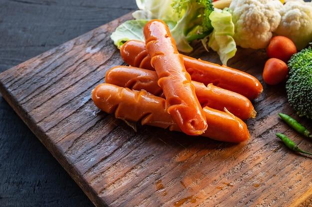 Worsten en groenten op een houten snijplank Premium Foto