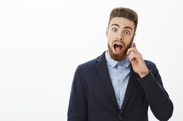 Wow, mijn bedrijf heeft nog een miljoen opgehaald. opgewonden en verbaasd knappe volwassen man met blauwe ogen en baard in formeel pak met smartphone in de buurt van oor schokkende details leren, verbaasd verbaasd laten vallen Gratis Foto