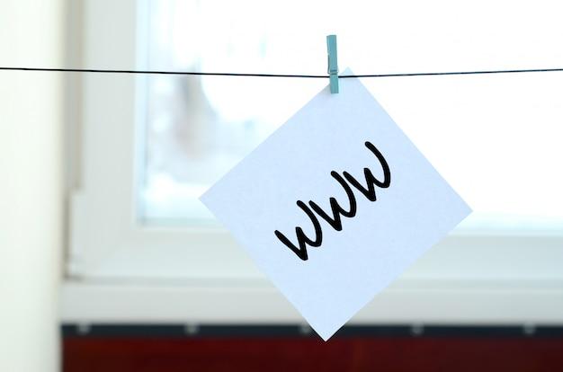 Www. opmerking is geschreven op een witte sticker die met een wasknijper aan een touw op een achtergrond van vensterglas hangt Premium Foto