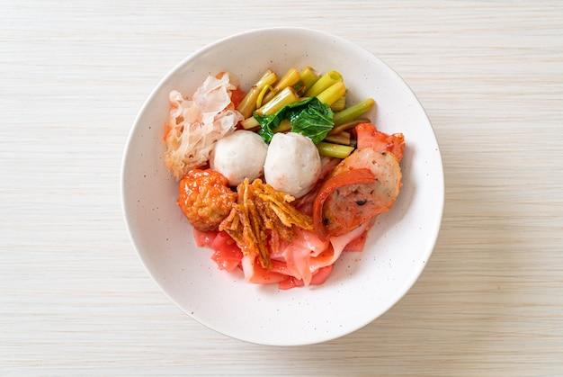 (yen-ta-four) - droge thaise stijlnoedel met diverse tofu en visbal in rode soep - aziatische eetstijl Premium Foto