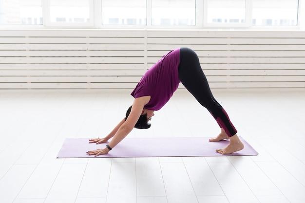 Yoga, mensen concept. een vrouw van middelbare leeftijd die yoga doet in de sportschool Premium Foto