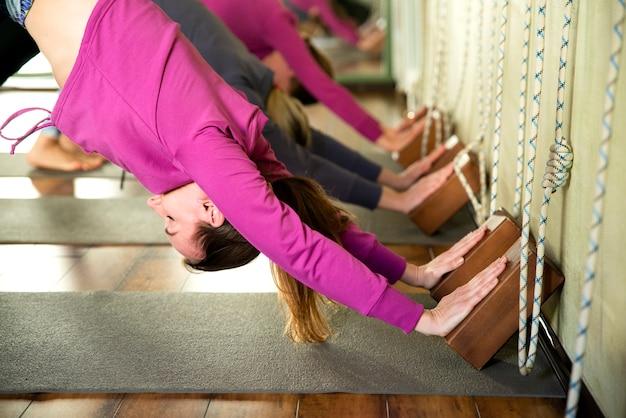 Yogaklasse, groep mensen die en yoga ontspannen doen stellen tegen muur. wellness en een gezonde levensstijl. Premium Foto