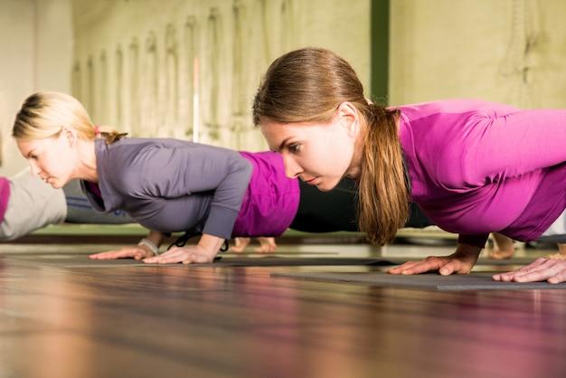 Yogaklasse, groep mensen ontspannen en yoga doen poseren. wellness en een gezonde levensstijl. Premium Foto