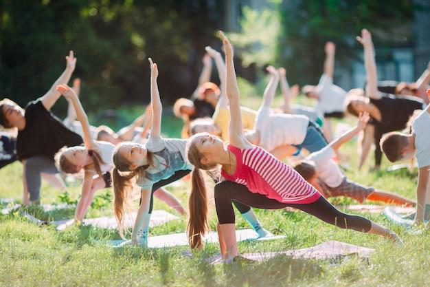 Yogalessen buiten in de open lucht. kinderyoga, Premium Foto