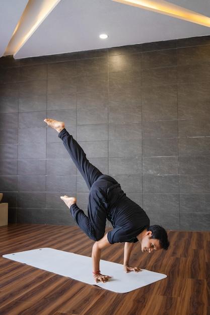 Yogi doet geavanceerde hand staan yoga pose in de sportschool Gratis Foto