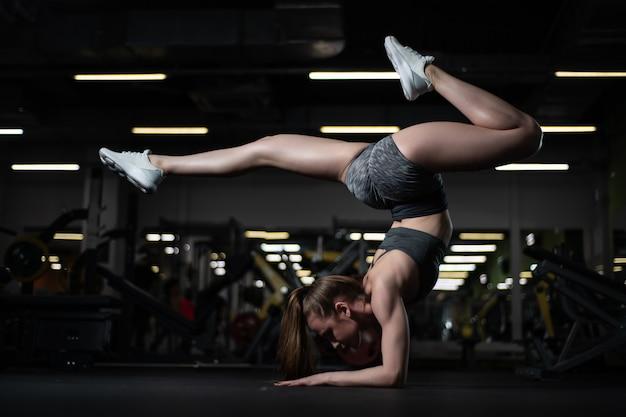 Yogi meisje doet geavanceerde inversie en arm-balans scorpion handstand. Premium Foto