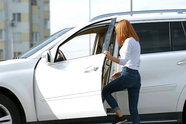 Yong mooie vrouw die zich in de buurt van een grote terreinwagen buitenshuis. bestuurdersmeisje in vrijetijdskleding buiten haar voertuig. Premium Foto