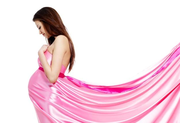 Youn mooie zwangere vrouw in roze jurk - witte muur Gratis Foto