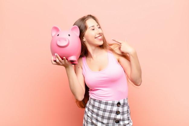 Yound blonde vrouw glimlachend vol vertrouwen wijzend naar eigen brede glimlach, positieve, ontspannen, tevreden houding met een spaarvarken Premium Foto