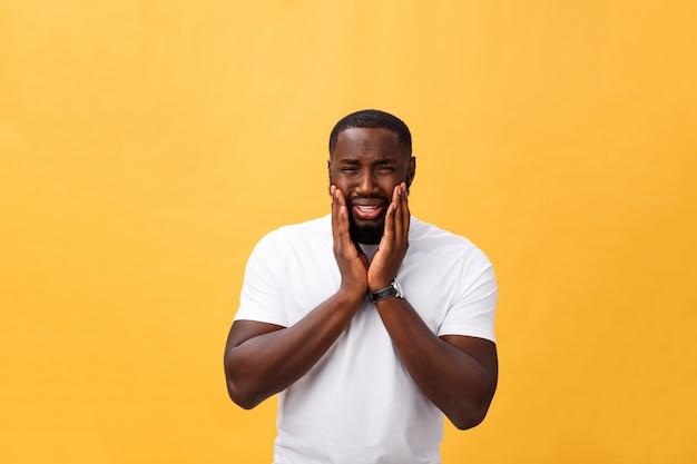 Young benadrukt man met de hand op zijn gezicht toont verdriet en wanhoop. geïsoleerd op gele achtergrond. Premium Foto