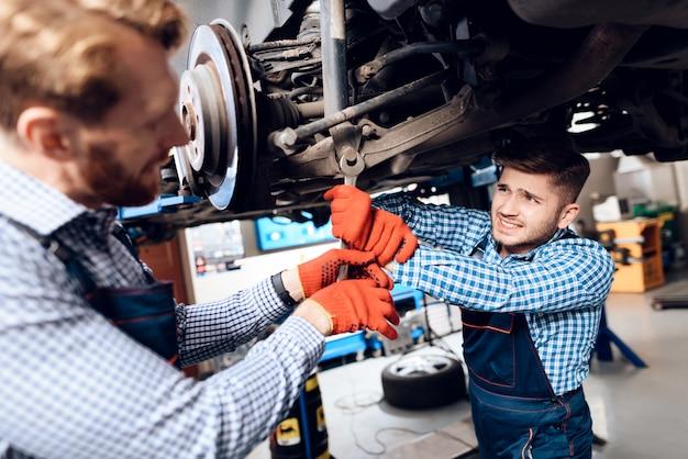 Young mechanics repairs automotive hub in garage. Premium Foto