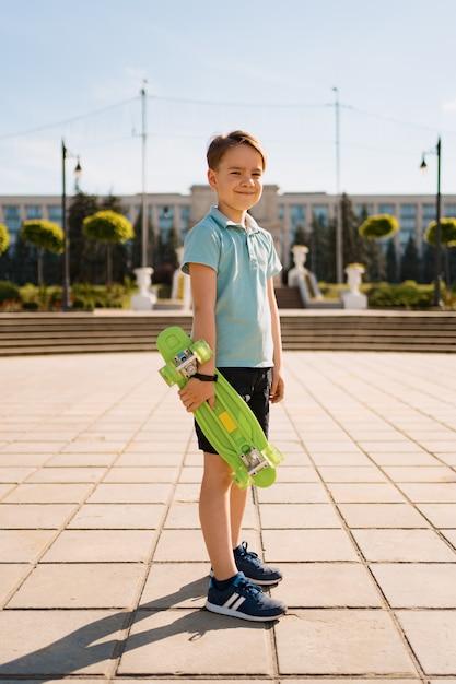 Young school cool boy in lichte kleding staat met penny board in de handen Gratis Foto