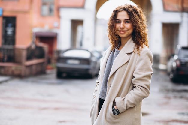 Younvrouw met krullend haar buiten de straat Gratis Foto