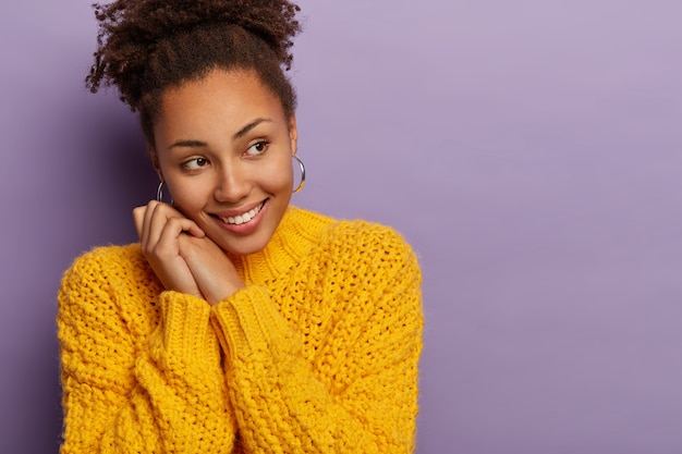 Zacht glimlachende donkere vrouwelijke modellen kijkt graag opzij, houdt de handen bij elkaar in de buurt van het gezicht, merkt wenselijk iets op, draagt een gebreide gele trui Gratis Foto