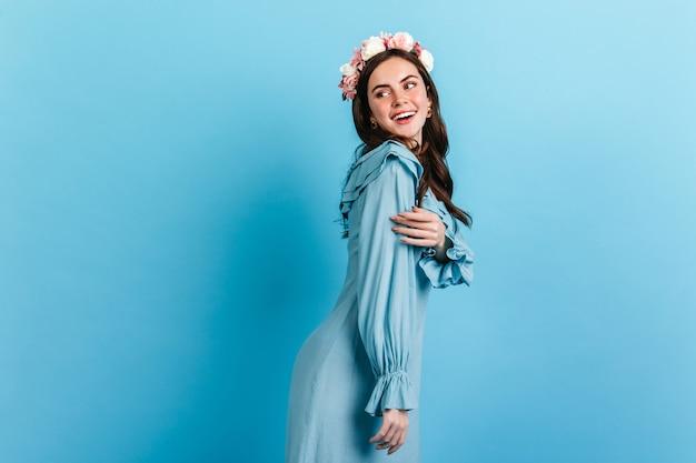 Zacht meisje met sneeuwwitte glimlach kijkt rond. model met kroon van bloemen en zijden jurk poseren op blauwe muur. Gratis Foto