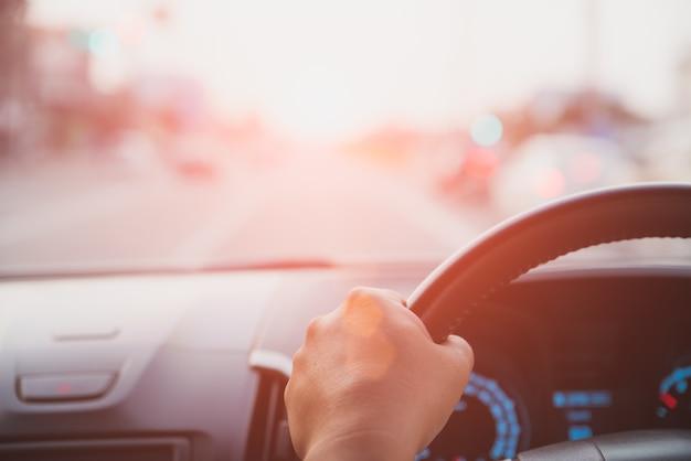 Zacht nadrukbestuurderhand die stuurwiel houden terwijl het drijven op de weg. Premium Foto