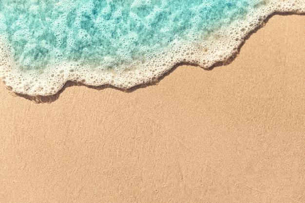 Zachte golf die op leeg zandig strand, de zomerachtergrond wordt omwikkeld. kopieer ruimte. Premium Foto