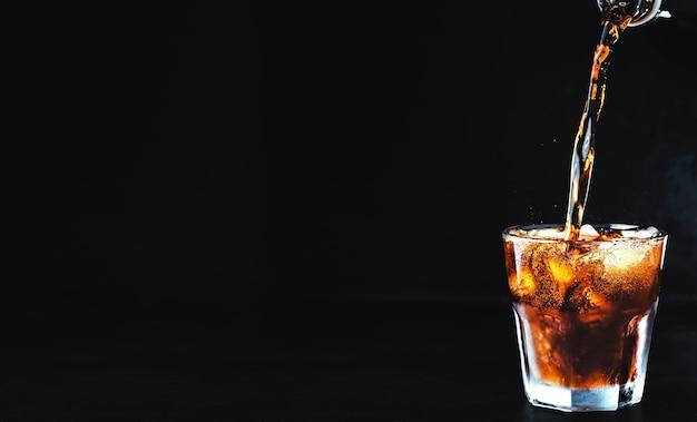 Zachte koolzuurhoudende coladrank wordt in een glas ijs gegoten Gratis Foto