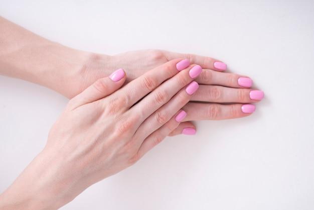 Zachte roze manicure. vrouwelijke handen op een witte achtergrond Premium Foto