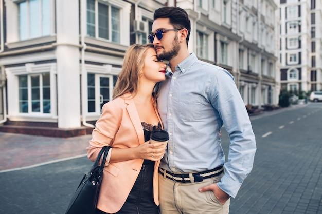 Zachtjes paar knuffelt op straat in de stad. knappe jongen is blauw shirt en zonnebril ziet er serieus uit, mooi blond meisje in zwarte jurk knuffelt hem. Gratis Foto