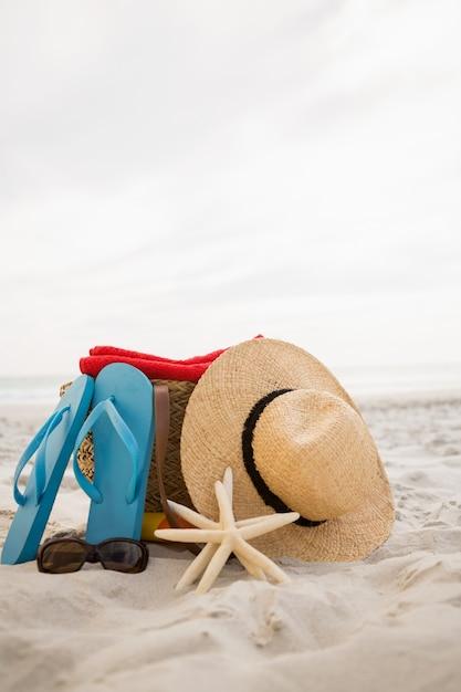Zak en strand accessoires gehouden op zand Gratis Foto