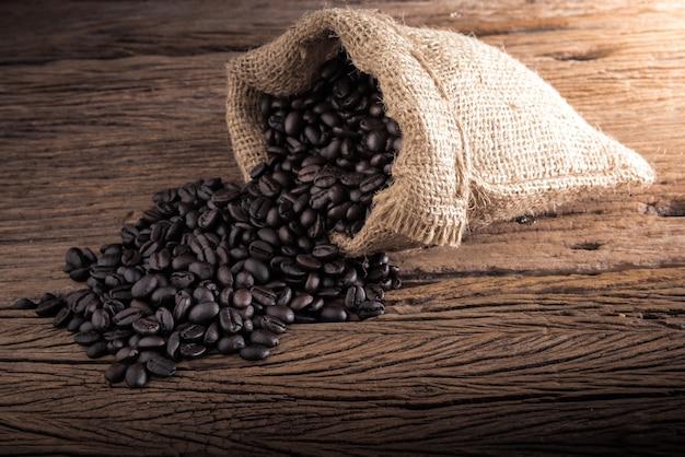 Zak koffiebonen verspreid op de houten tafel Premium Foto