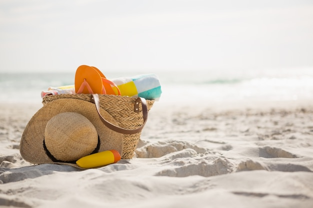 Zak met strand accessoires gehouden op zand Gratis Foto