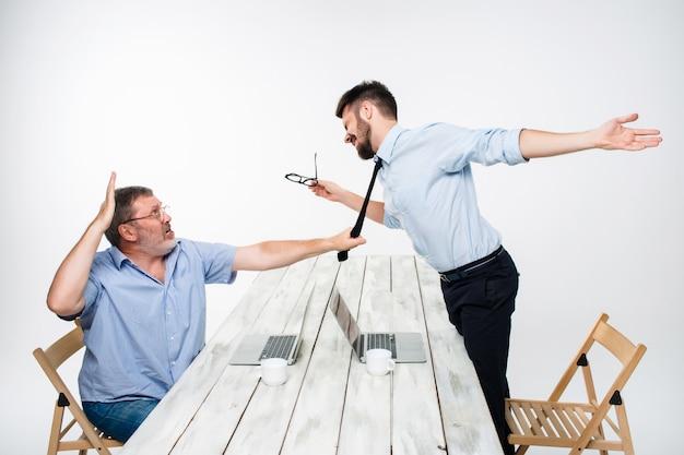 Zakelijk conflict. de twee mannen uiten negativiteit terwijl een man de stropdas van haar tegenstander vastpakt Gratis Foto