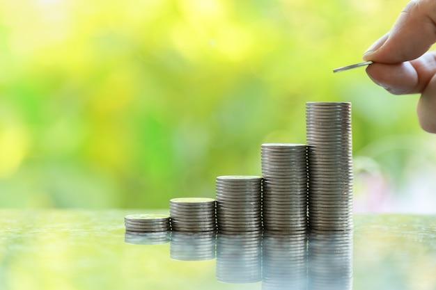 Zakelijk, geld, sparen en beveiligingsconcept. sluit omhoog van de holding van de mensenhand en zet een muntstuk bovenop stapel muntstukken met bokeh van de groene achtergrond van de bladaard en exemplaarruimte. Premium Foto