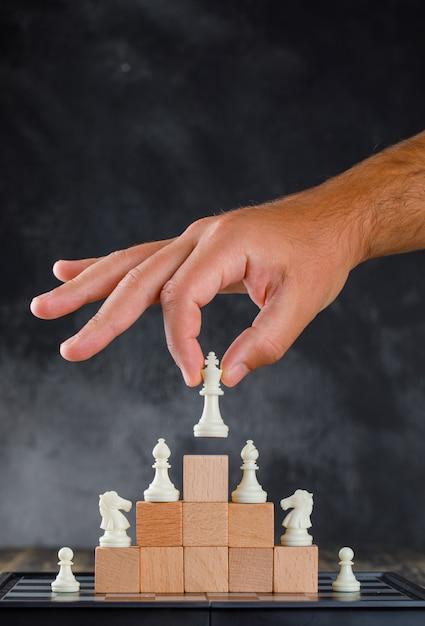 Zakelijk succes concept met schaakbord zijaanzicht. man figuur op piramide van blokken plaatsen. Gratis Foto