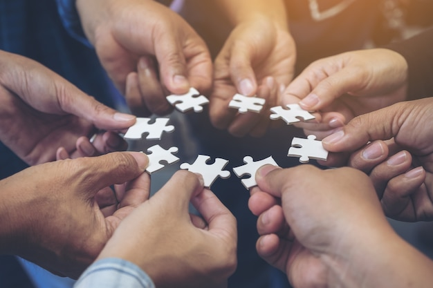 Zakelijk team staan en hun puzzel samen overhandigen Premium Foto
