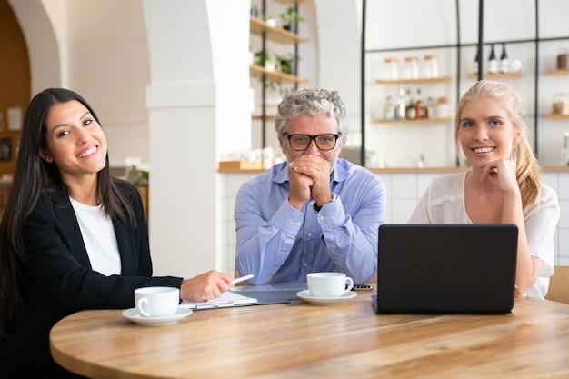 Zakelijke collega's of partners van verschillende leeftijden ontmoeten elkaar tijdens een kopje koffie bij co-working, zittend aan tafel met laptop en documenten, Gratis Foto
