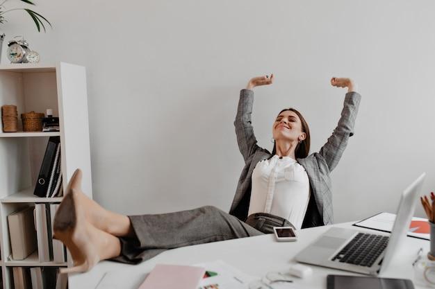 Zakelijke dame tevreden met het werkresultaat met plezier gooide haar benen naar het witte bureaublad. Gratis Foto