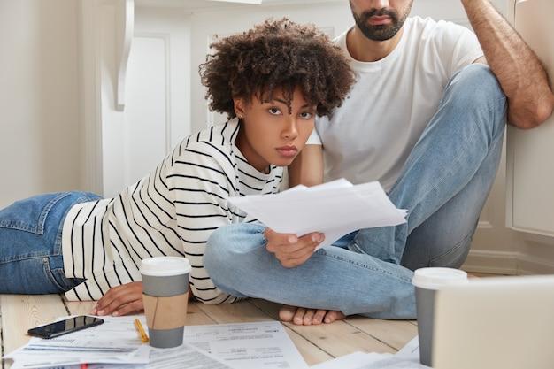 Zakelijke multi-etnische vrouwelijke en mannelijke collega's denken na over financieel verslag Gratis Foto