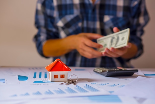 Zakelijke onroerend goed concept, huis model met een sleutel en dollarbiljetten zetten op papier grafiek op houten achtergrond. Premium Foto