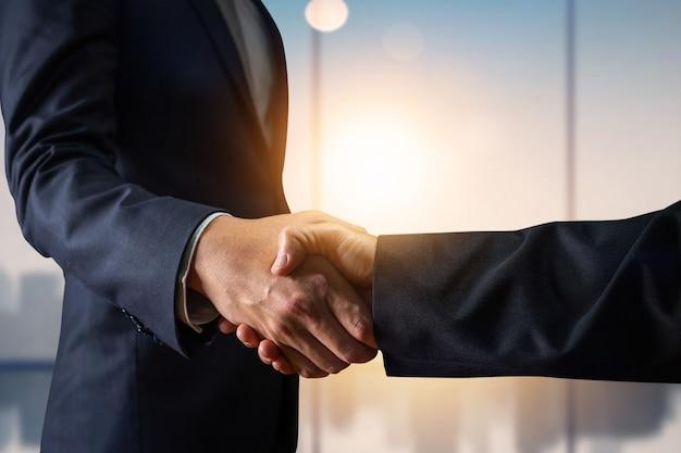 Zakelijke overeenkomst en succesvol onderhandelingsconcept, zakenman in de hand van de kostuumschok met klant Premium Foto