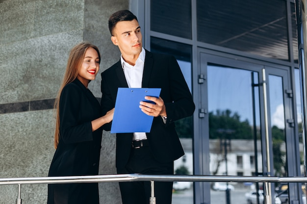 Zakelijke partners man en vrouw naast een bedrijfsgebouw met een document. - afbeelding Premium Foto