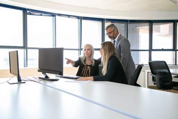 Zakelijke professionals kijken samen naar presentatie op computermonitor, project bespreken, zitten op de werkplek en wijzen op display. zakelijke communicatie of teamwerk concept Gratis Foto