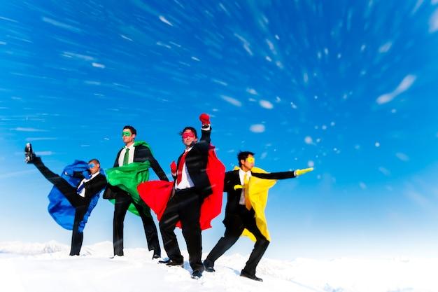 Zakelijke superhelden poseren in de sneeuwstorm Premium Foto