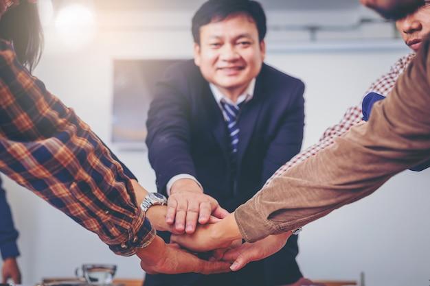 Zakelijke volkeren sluiten zich aan bij hun handen. teamwerk krachtig delen tijdens een vergadering. Premium Foto